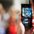 Kvinna håller i mobiltelefon och filmar.